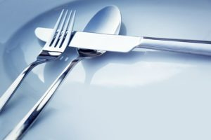 Restaurant menu series. Wedding or dinner table place setting. Fork and knife and glass in elegant setting with copyspace